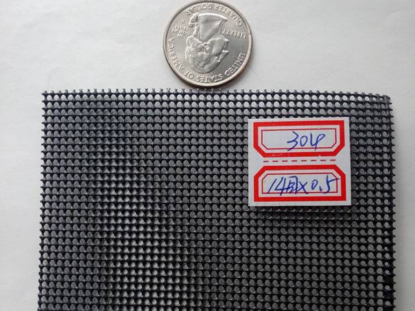 A piece of grey security screen with a white label is beside a metal coin.