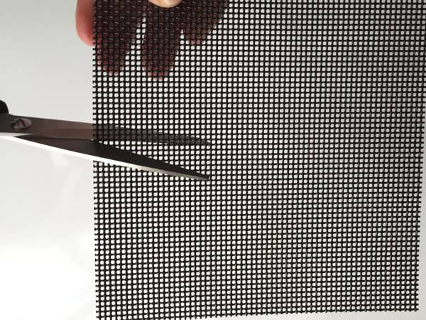 A scissor is shearing a piece of black security screen.