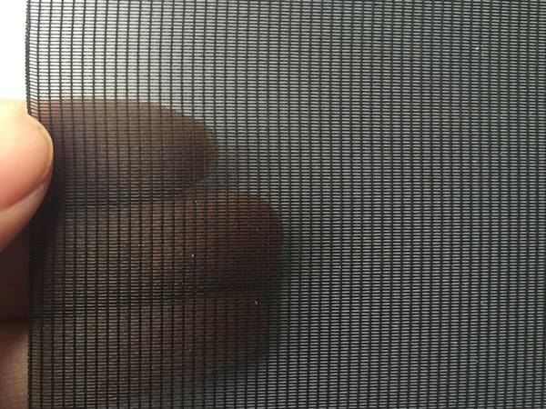A hand is holding a piece of anti pollen screen.